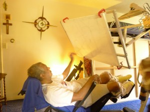 Figure 2: Client using the modified easel from his wheelchair in a reclined position.