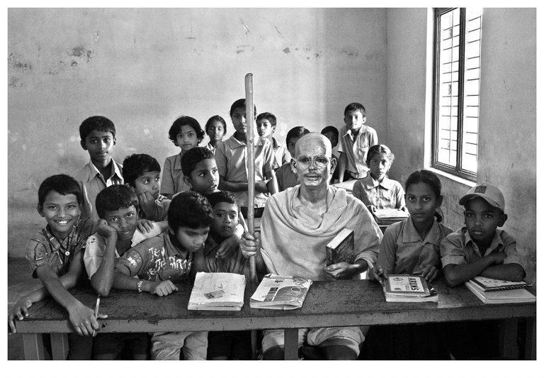 Fig. 2. Cop Shiva, Byagadehalli Basavaraju as Gandhi with rural school children, Karnataka, photograph from the <em>Being Gandhi</em> series, 2012 <br />© Cop Shiva, 2012