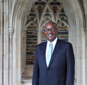 Kerry Haynie in suit in front of gothic architecture