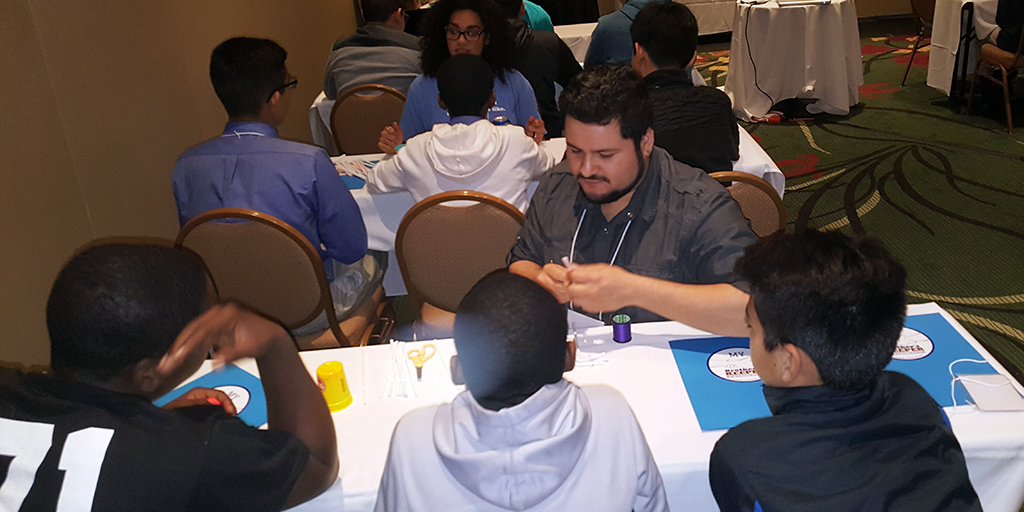 Angelo Moreno, a graduate student in molecular genetics and microbiology, works with students from Durham schools at an event hosted by Made in Durham and My Brother's Keeper Durham.