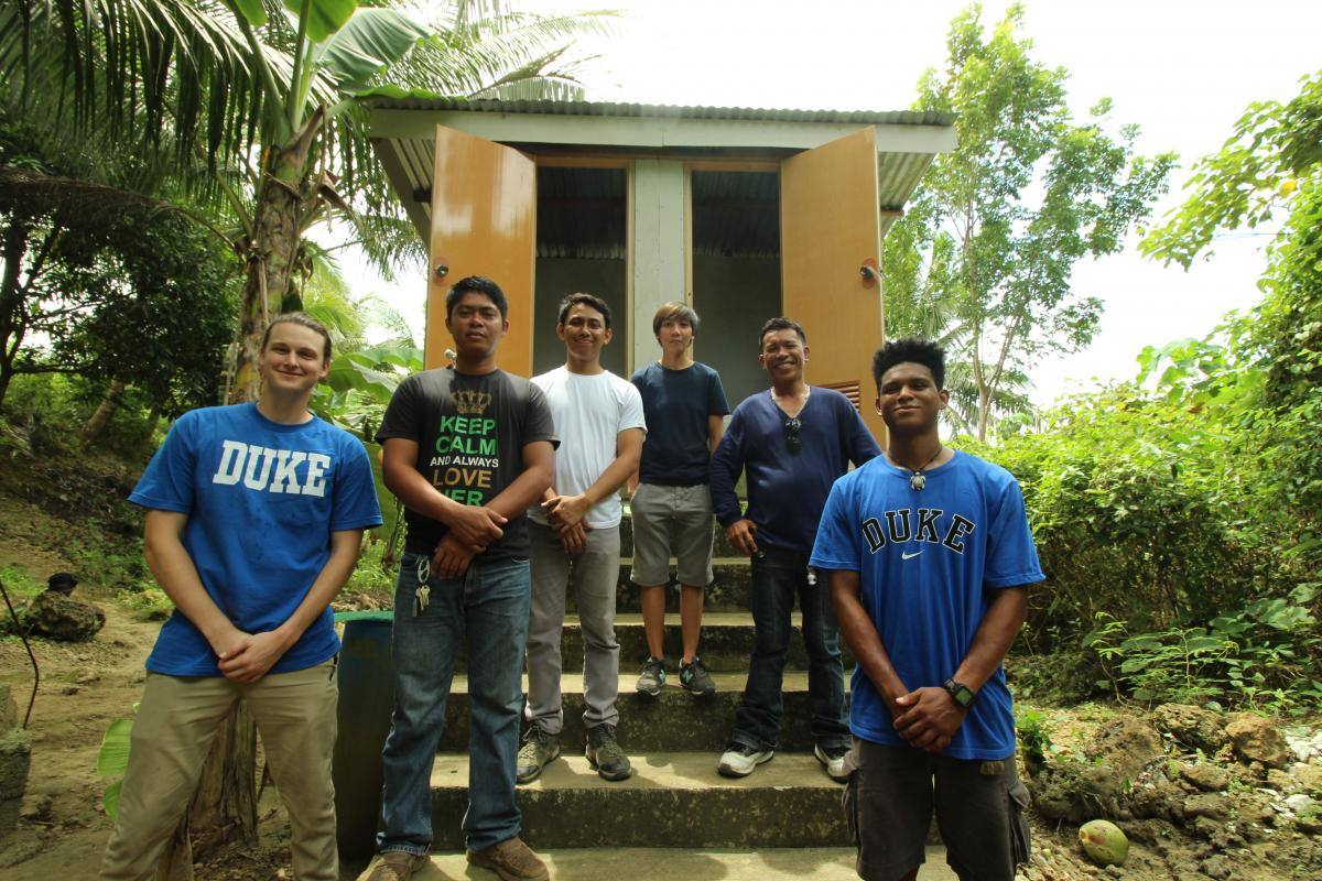 Graham Miller (far left) and Brandon Hunter (far right) of the Duke ADPL team pose with their collaborators from the Tesari Foundation (center) in front of the ADPL system in Baragay Subayon, Toledo City, Cebu, Philippines.