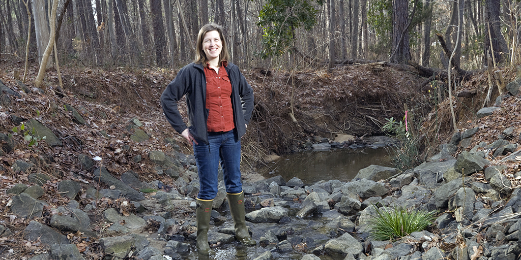 Emily Bernhardt at a creek outside the Phytotron Building on Duke's campus (Photo: Megan Morr).