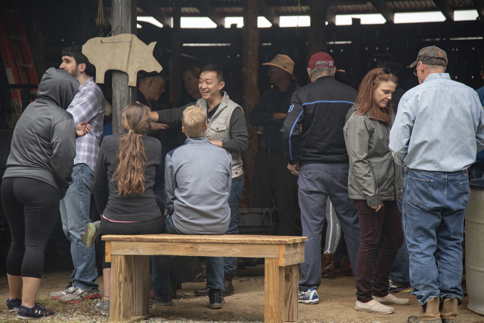 party goers gather under the shelter of the barn during a period of light rain