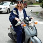 Picture of Kathryn on a scooter in her faculty regalia