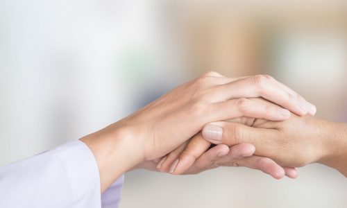 doctor hand comforting patient in a hospital room background