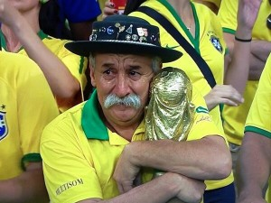 Courtesy of Gaúcho da Copa Twitter - Iconic image of a crying Brazilian fan clutching the World Cup trophy as he mourns Brazil's loss to Germany.